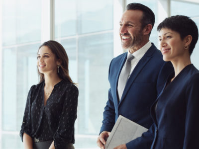 Cropped shot of a diverse group of businesspeople standing together and smiling after a successful meeting in the office